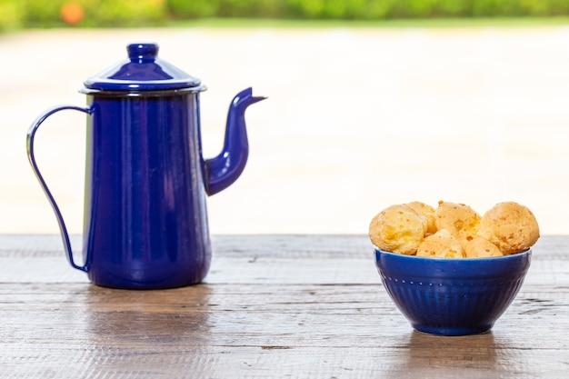 Pain au fromage, restauration rapide brésilienne, sur une table rustique, avec un fût de café et de la nature en arrière-plan.