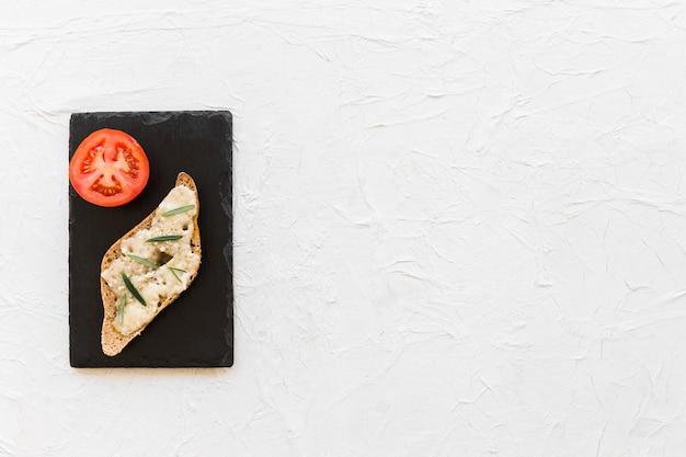 Pain au fromage avec une tranche de tomate sur la plaque d'ardoise sur le fond blanc
