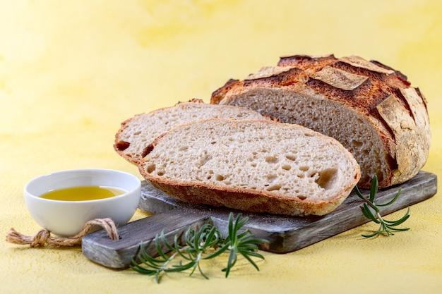 Pain au levain bio artisanal tranché, huile d'olive et romarin frais
