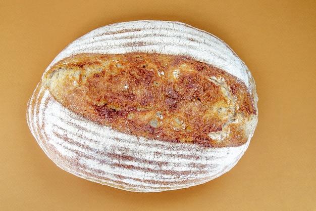 Pain au levain biologique fraîchement cuit isolé sur fond marron ou café. une miche de délicieux pain de sarrasin frais. nourriture écologique. vue de dessus, mise à plat.