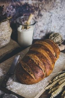 Un pain au levain avec des épis de blé de côté et un récipient avec de la farine derrière