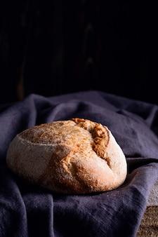 Pain au levain fait maison fraîchement cuit sur une serviette en lin foncé, fond en bois.