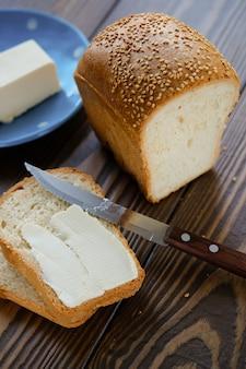 Pain au sésame et beurre sur une table en bois.