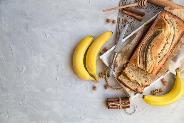 Pain aux bananes maison frais dans un plateau en bois blanc avec des ingrédients sur du béton léger