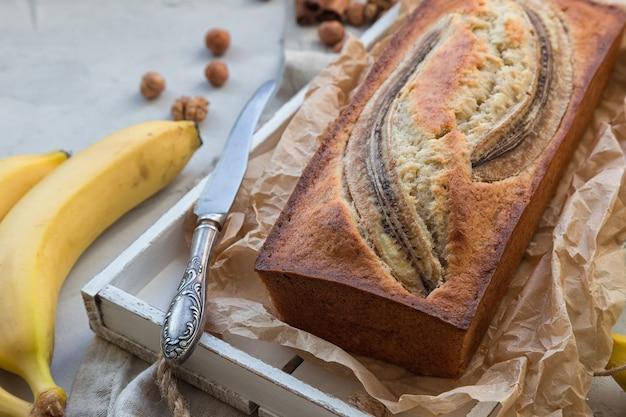 Pain aux bananes maison frais dans un plateau en bois blanc avec des ingrédients sur du béton léger.