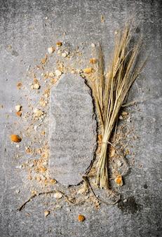 Pain aux épis de blé et support en pierre. sur la table en pierre. espace libre pour le texte. vue de dessus