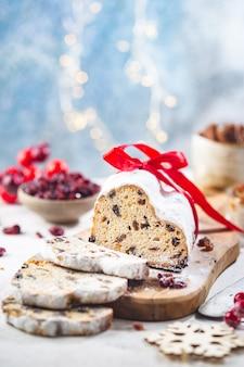 Pain aux fruits sucrés traditionnels stollen de noël avec réglage de la table de vacances de noël au sucre glace