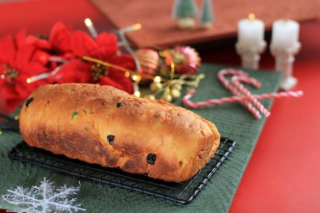 Pain aux fruits traditionnel stollen de noël friandises de vacances volées pour la famille avant de saupoudrer de sucre en poudre, fraîchement cuites au four