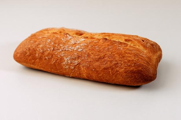 Pain aux grains sans gluten frais avec des graines sur fond blanc.