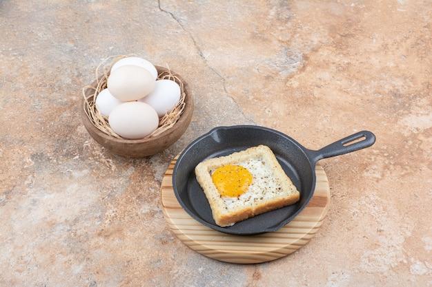 Pain aux œufs au plat sur une poêle noire avec un bol d'oeufs