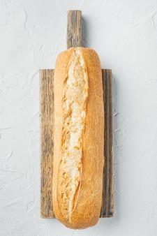 Pain baguette artisanal, sur fond blanc, vue de dessus à plat