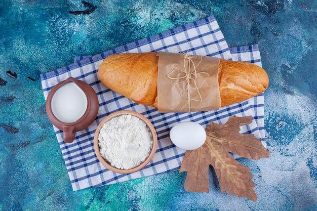 Pain baguette, farine, oeuf et lait sur torchon sur bleu.