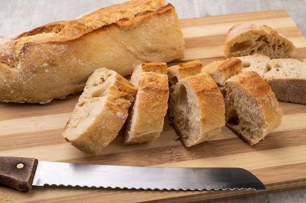 Pain baguette français traditionnel fait maison avec des tranches sur planche de bois.
