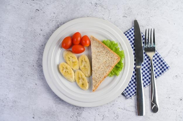 Pain, banane et tomate sur une plaque blanche avec une fourchette et un couteau.