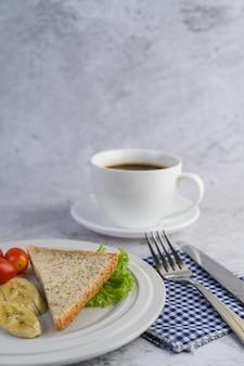 Pain, banane et tomate sur une plaque blanche avec une tasse de café, une fourchette et un couteau.
