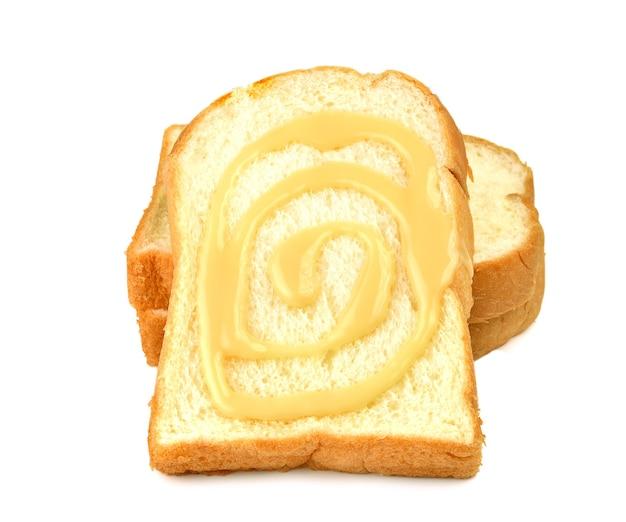 Pain, beurre, crème, lait concentré sucré sur blanc