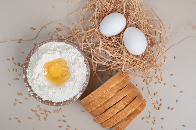 Pain blanc frais tranché avec bol en bois plein de farine