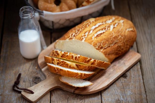 Pain blanc sur une planche de bois. le pain de la boulangerie vient de sortir du four. cuisson fraîche sur une table en bois.