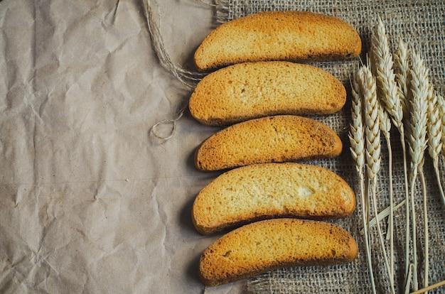 Pain blanc sec de biscotte sur toile et papier et épillets de seigle mûrs