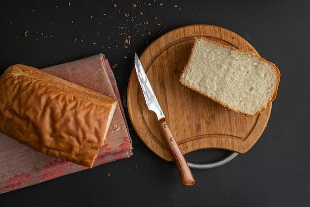 Pain blanc tranché fraîchement cuit au four avec un couteau en métal, toasts pour la cuisson des sandwitchs