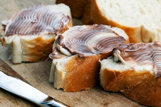 Pain blanc tranché avec pâte à tartiner au beurre de chocolat doux, beurre de chocolat doux et pain blanc, pâte de chocolat au cacao naturel pendant le petit déjeuner