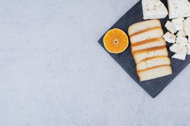 Pain blanc tranché avec tranche d'orange sur une planche à découper. photo de haute qualité