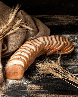 Pain blanc en tranches de pain blanc avec du blé et de la farine sur table