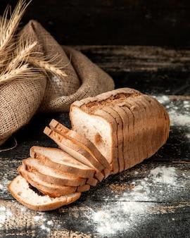 Pain blanc en tranches de pain blanc avec de la farine et du blé sur la table
