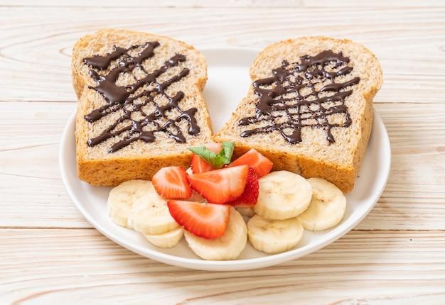 Pain de blé entier avec banane fraîche, fraise et chocolat