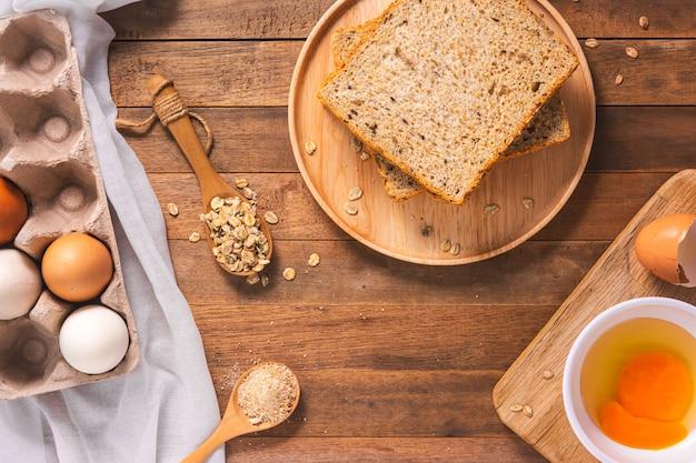 Pain de blé entier cuit sur un plateau en bois et ingrédient à cuire