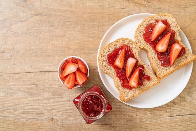 Pain de blé entier fait maison avec confiture de fraises et fraises fraîches