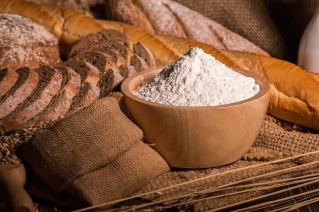 Pain de blé entier, farine et sac en tissu sur une table en bois.