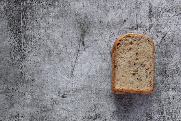 Pain de blé entier à grains tranchés sur fond de bois rustique foncé, ingrédients bio, aliments sains, vue de dessus.