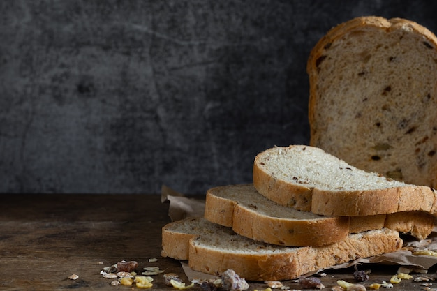 Pain de blé entier à grains tranchés sur fond de bois rustique foncé, ingrédients bio, aliments sains.