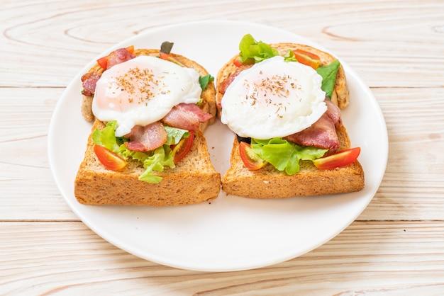 Pain de blé entier grillé avec légumes, bacon et œuf ou œuf bénédictine pour le petit déjeuner