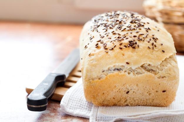 Pain de blé fait maison avec des graines de lin sur une table de cuisine