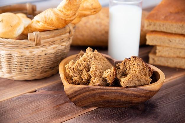 Pain cassé en morceaux dans une assiette en bois et d'autres types de produits de boulangerie avec un verre de lait sur une table sombre