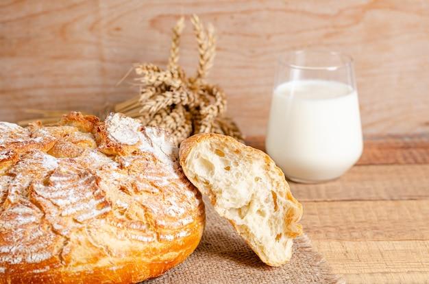 Pain cassé de pain de farine de blé sur un sac sur un fond en bois.