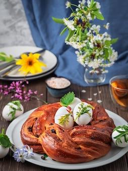 Pain challah aux raisins secs, cardamome et vanille sur un plat blanc