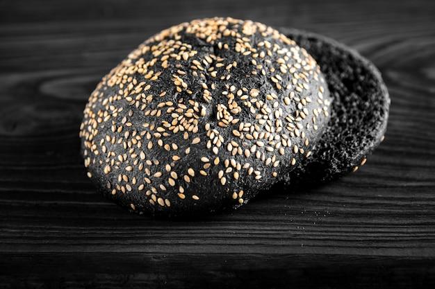 Pain de charbon de bois, pain noir isolé sur fond de bois.