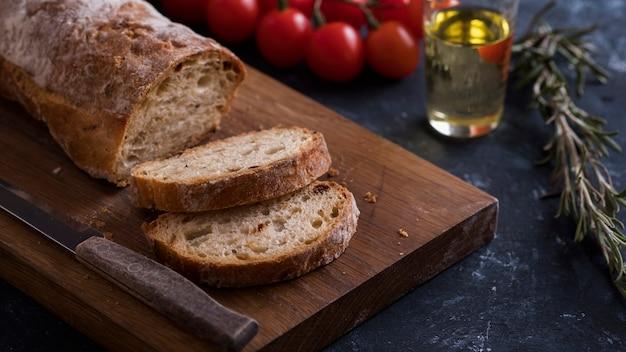 Pain ciabatta croustillant fait maison sur une planche à découper en bois avec des tomates et de l'huile d'olive. pain frais