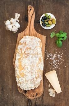 Pain ciabatta fraîchement sorti du four avec de l'ail, des olives méditerranéennes, du basilic et du parmesan sur une planche de service