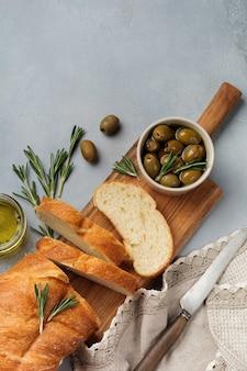 Pain ciabatta traditionnel italien aux olives, huile d'olive, poivre et romarin sur fond de pierre ou de béton gris clair. mise au point sélective vue de dessus. copiez l'espace.