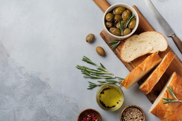 Pain ciabatta traditionnel italien aux olives, huile d'olive, poivre et romarin sur pierre gris clair ou surface en béton