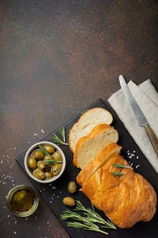 Pain ciabatta traditionnel italien aux olives, huile d'olive, poivre et romarin sur une pierre sombre ou une surface en béton