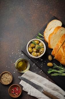 Pain ciabatta traditionnel italien aux olives, huile d'olive, poivre et romarin sur une surface de béton sombre