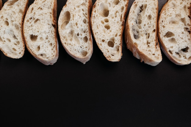 Pain ciabatta en tranches sur fond noir. pain blanc italien. vue de dessus avec espace de copie.