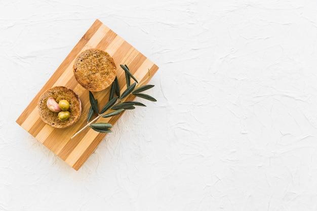 Pain circulaire aux olives et gousse d'ail avec brindille sur planche à découper
