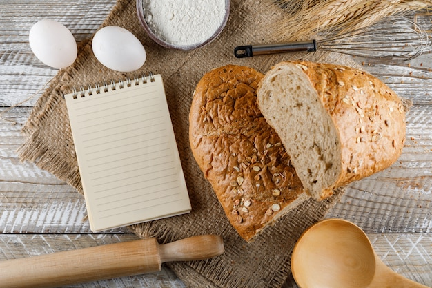 Pain coupé en deux avec un bloc-notes, des œufs, un rouleau à pâtisserie sur un tissu de sac et une surface en bois, vue de dessus.