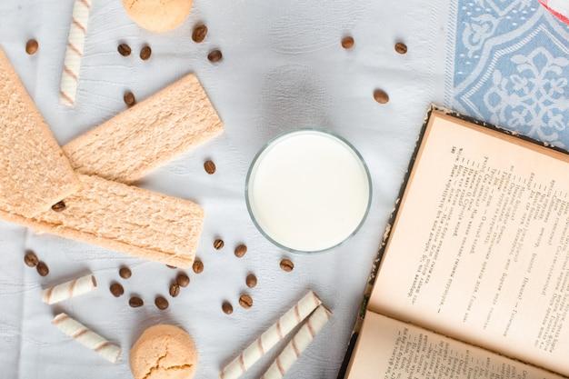 Pain craquelin et biscuits avec un verre de lait et un livre de côté